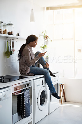 Buy stock photo Shot of a young woman sitting on her kitchen counter using the phone