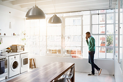 Buy stock photo Shot of a young man using his cellphone in the kitchen