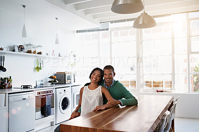Buy stock photo Portrait of a smiling young couple sitting in their kitchen