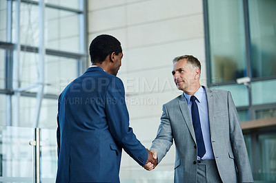 Buy stock photo Shot of of two businessmen shaking hands in the lobby of an office building