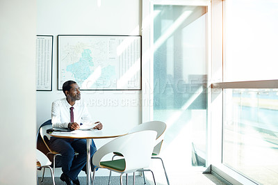 Buy stock photo Shot of a businessman looking out of a window while sitting at a table reading paperwork