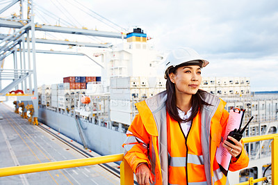Buy stock photo Shot of a woman in workwear standing on a commercial dock holding a walkie talkie