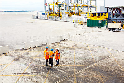 Buy stock photo High angle shot of three workers talking together while standing on a commercial dock