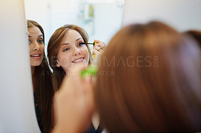 Buy stock photo Shot of two young friends putting on mascara in the bathroom mirror