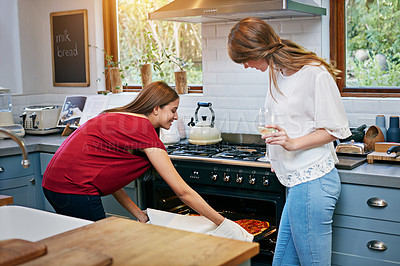 Buy stock photo Shot of two young friends making pizza together