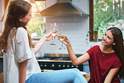 Buy stock photo Shot of two friends in a kitchen toasting each other while drinking wine