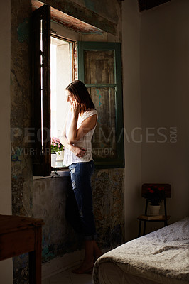 Buy stock photo Shot of a young woman standing in her kitchen talking on a cellphone
