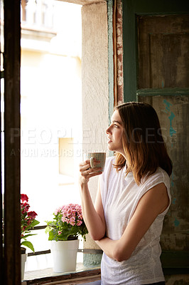 Buy stock photo Shot of a young woman drinking a cup of coffee while looking out of a window
