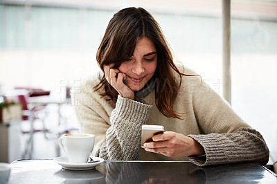 Buy stock photo Shot of a young woman using a cellphone while sitting in a cafe