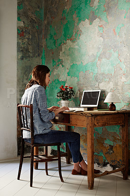 Buy stock photo Shot of a young woman sitting at a work desk at home working on a laptop