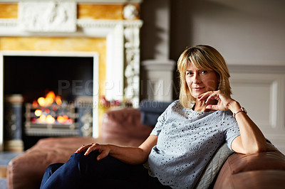 Buy stock photo Portrait of a mature woman relaxing on her living room sofa with a fire glowing in the background