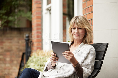 Buy stock photo Shot of a mature woman sitting on her front porch using a digital tablet