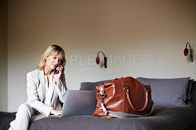 Buy stock photo Shot of a mature businesswoman sitting on a hotel bed talking on her cellphone