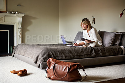 Buy stock photo Shot of a mature businesswoman lying on a hotel bed taking notes while using a digital tablet