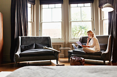 Buy stock photo Shot of a mature woman working on a laptop and reading paperwork in her living room after a trip