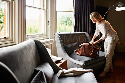 Buy stock photo Shot of a mature woman unpacking at home after a trip