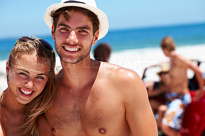 Buy stock photo Portrait of a young couple at the beach with friends in the background