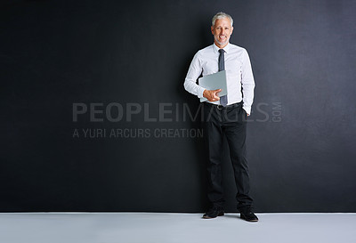 Buy stock photo Studio portrait of a mature businessman standing against a black background