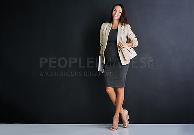 Buy stock photo Studio portrait of a young pregnant businesswoman standing against a black background