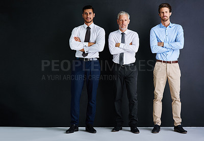 Buy stock photo Studio portrait of three businessman standing against a black background