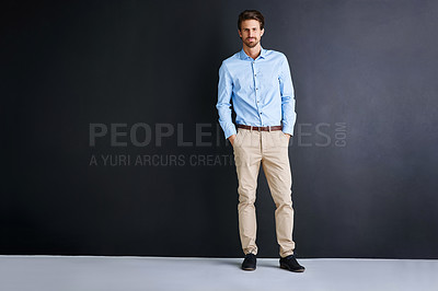 Buy stock photo Studio portrait of a young businessman standing against a black background
