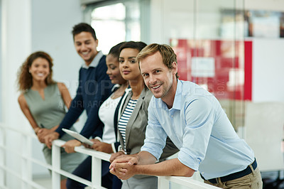 Buy stock photo Portrait of a group of smiling coworkers leaning on a railing in an office