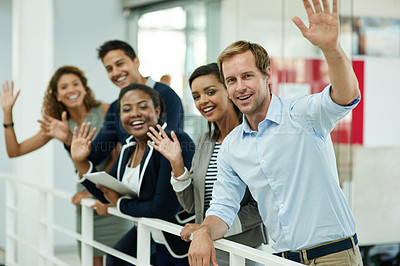 Buy stock photo Portrait of a group of smiling coworkers waving while leaning on a railing in an office