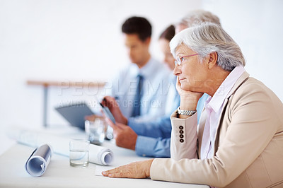 Buy stock photo Portrait of a bored old business woman sitting with colleagues on business meeting in office