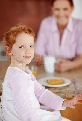 Buy stock photo Portrait of a little girl having her breakfast with a blur mature woman in background