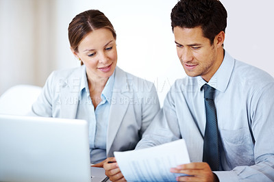 Buy stock photo Portrait of a successful young business colleagues reading document with laptop in front