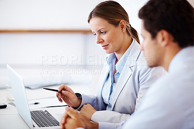 Buy stock photo Portrait of a beautiful young businesswoman working on laptop with her colleague at office