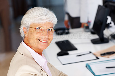 Buy stock photo Portrait of a happy old businesswoman sitting by the desk at office