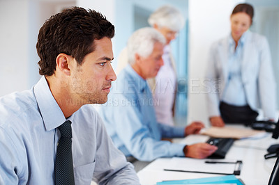 Buy stock photo Smart young male business executive working at office with colleagues in discussion in background