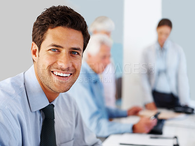 Buy stock photo Happy young male business man sitting at office with colleagues in background