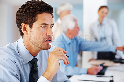 Buy stock photo Portrait of a thoughtful young male business executive sitting at office with colleagues blurred in background