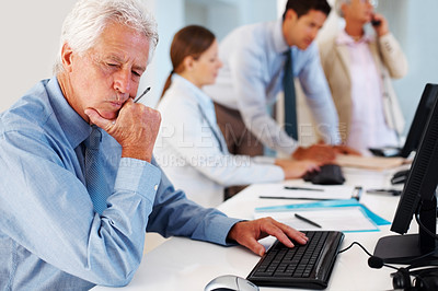 Buy stock photo Mature businessman sits thoughfully in front of his computer with colleagues blurred in background