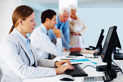 Buy stock photo Pretty young business woman working on computer with colleagues in background