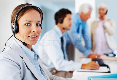 Buy stock photo Smiling customer care representative wearing headset with colleagues in background