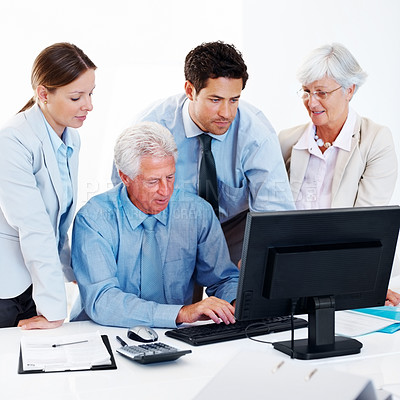 Buy stock photo Smart mature businessman giving presentation on computer to his colleagues in office