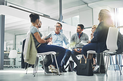 Buy stock photo Shot of a group of coworkers talking together while sitting in a circle in an office