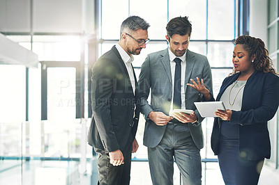 Buy stock photo Shot of a group of coworkers talking together over a digital tablet in an office