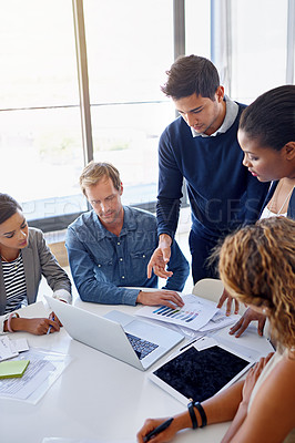 Buy stock photo Shot of a group of coworkers working together on a laptop in an office