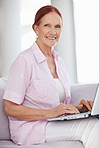 Happy senior woman sitting in sofa while working on a laptop