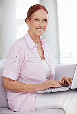 Buy stock photo Portrait of a happy senior woman sitting in sofa while working on a laptop
