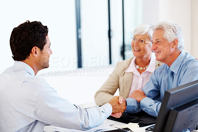 Buy stock photo Portrait of a happy old couple shaking hands with an insurance advisor at office