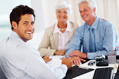 Buy stock photo Portrait of a happy male advisor with an old couple in background at his office desk