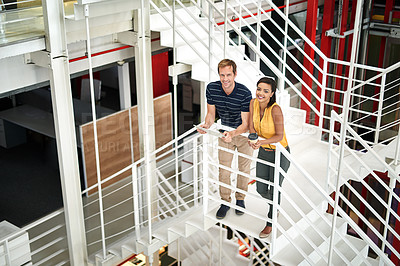 Buy stock photo Portrait of two smiling colleagues standing together on stairs in an office