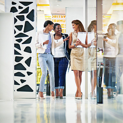 Buy stock photo Shot of a group of female coworkers talking together while walking down an office hallway
