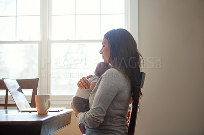 Buy stock photo Shot of a mother holding her newborn baby while sitting at a table in front of a laptop