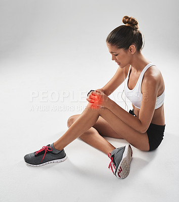 Buy stock photo Shot of a young woman holding her injured knee that's highlighted in red